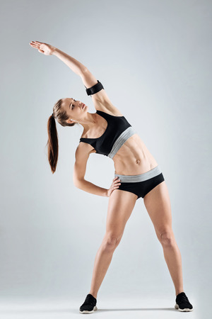 persistence: Motivated girl doing exercises on a grey background Stock Photo