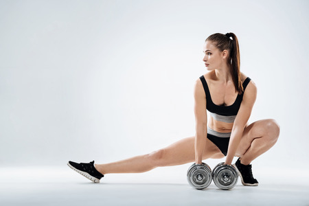 Young girl exercising with dumbbells on a grey background