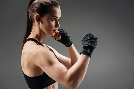 Athletic girl boxing on a grey background Stock Photo