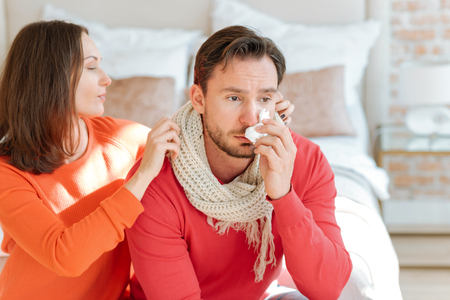 Helpful woman taking care about her boyfriend at home