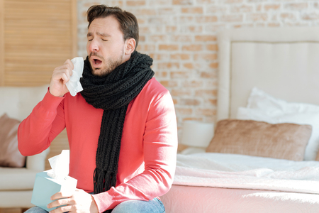 Young bearded man suffering from illness at home Stock Photo