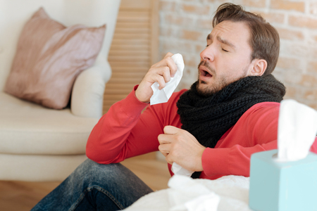 Helpless bearded man suffering from sickness at home Stock Photo