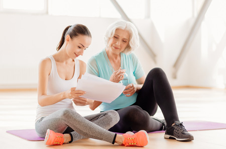 Attractive positive woman holding a fitness program Stock Photo
