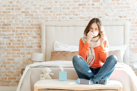 Upset young woman suffering from influenza at home Stock Photo