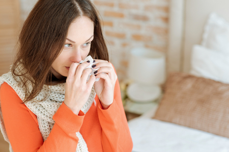 Involved young woman suffering from flu at home
