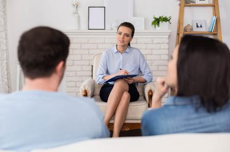 Pleasant family psychologist sitting cross legged