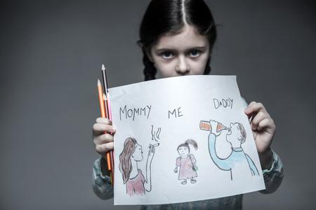 misbehavior: Little girl holding portrait of her family in both hands