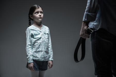 misbehavior: Little scared girl being afraid of the belt Stock Photo