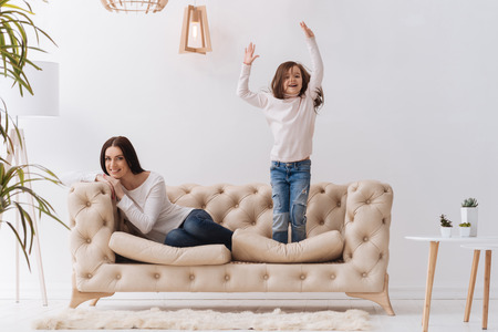 upbringing: Positive happy girl jumping on the sofa Stock Photo