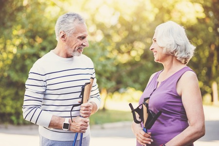 Positive aged couple holding walking poles