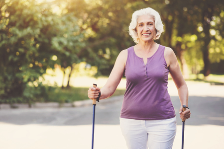 Happy aged woman walking in the park