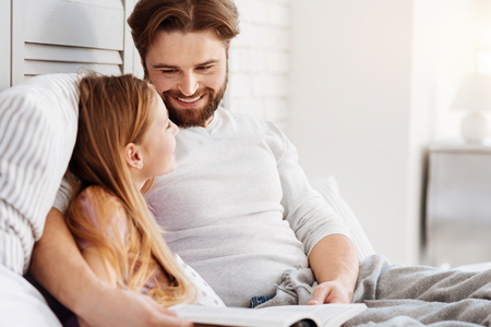 Smiling male person looking on his daughter Stock Photo