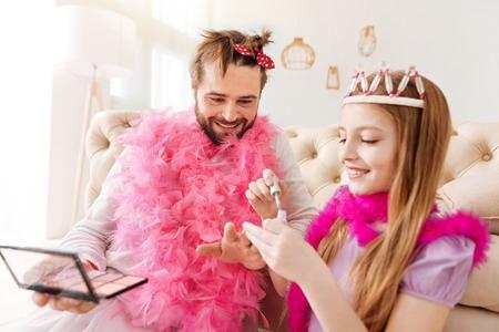 potěšen: Legrační muž používající kosmetiku při hraní s dcerou Reklamní fotografie