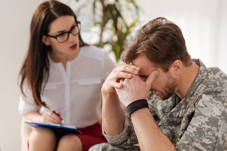 Unhappy cheerless soldier needing professional psychological help