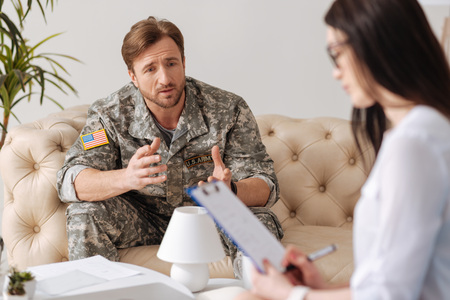 Depressed young soldier looking at his psychologist Stock Photo