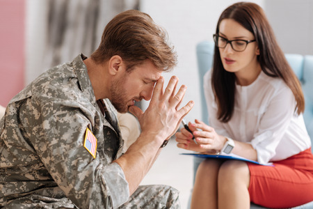 Unhappy stressed soldier trying to concentrate Stock Photo