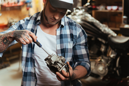 Close up of strong male holding detail from motorcycle Stock Photo