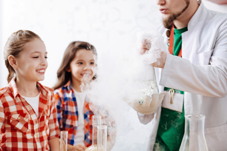 Delighted positive girls being surrounded by chemical smoke