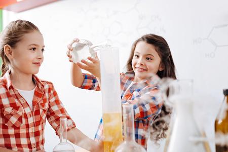 Joyful bright girl pouring a chemical liquid