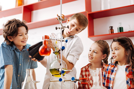 Happy delighted kids experimenting with chemical liquids