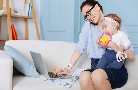 Talented charismatic woman combining motherhood and career Фото со стока