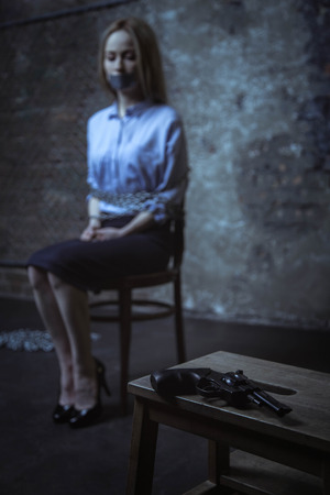 Frightened captured woman waiting in a dark room