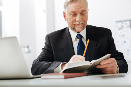 Diligent aged employer checking notes at work Stock Photo
