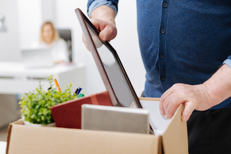 Fired man gathering personal belongings into the box Stock Photo