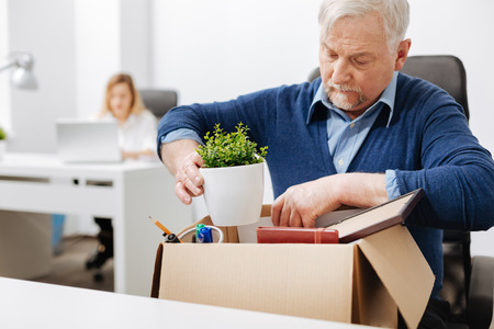 Desperate office manager gathering personal stuff into the box Stock Photo