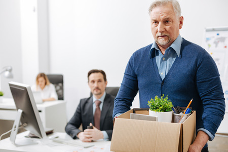 Impiegato anziano frustrato che lascia l'ufficio con la scatola piena di effetti personali Archivio Fotografico - 74244023