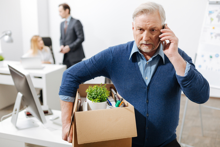 Puzzled old employee leaving office with the box full of belongings