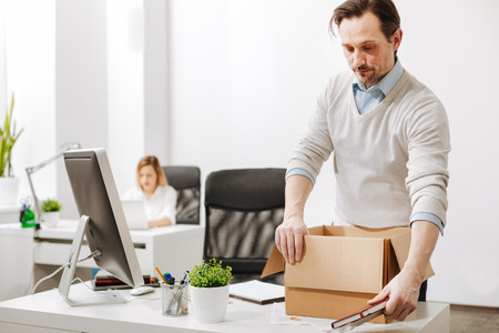 Confused staff member packing the box and leaving the company