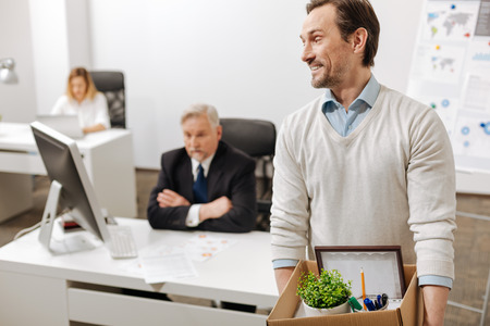 Fired smiling employee carrying the box and quitting the job