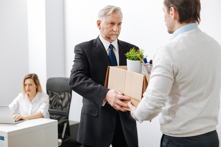 gerontology: Aged bearded employer giving the box to the employee