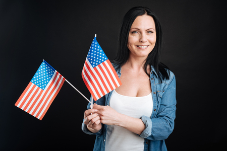 state of mood: Positive delighted female keeping flags Stock Photo