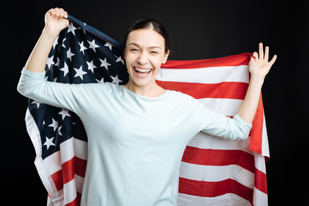 state of mood: Joyful brunette girl posing with big flag