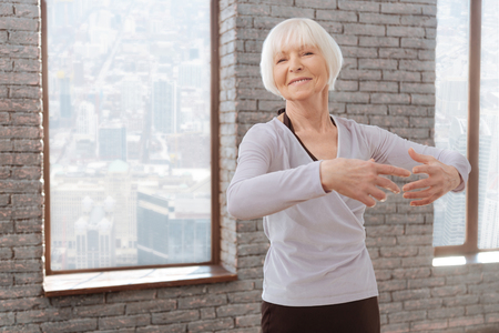Optimistic aging woman tangoing at the dance lesson