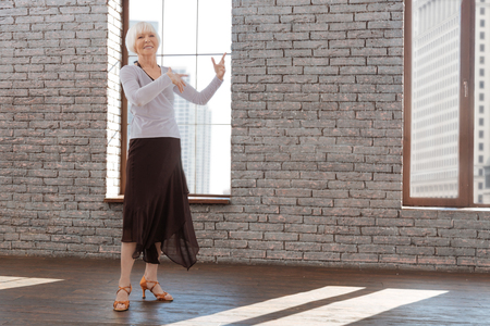 Positive senior woman performing at the dance lesson