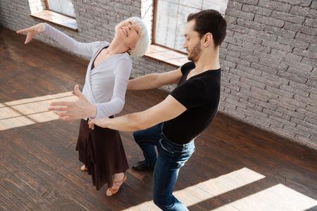 Positive dance couple tangoing in the ballroom Stock Photo