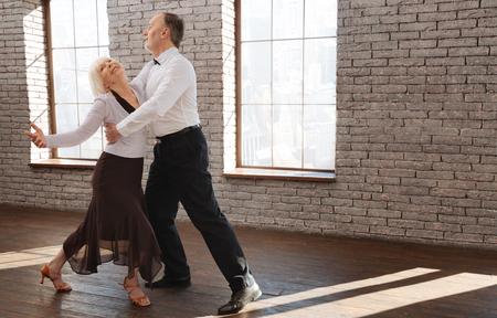Delighted senior couple enjoying tango at the ballroom