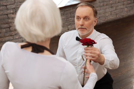 Confident old pensioner expressing love to woman in the ballroom