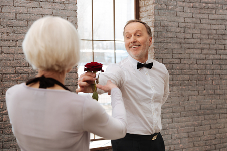 Smiling senior man dancing with aged woman in the ballroom Stock Photo