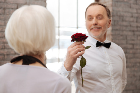 Handsome aged man dancing with aging woman in the ballroom