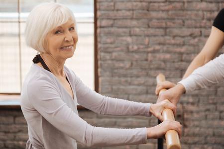 Happy charming pensioner dancing in the dance studio