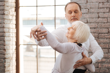 Smiling aged couple performing in interaction in the dance studio