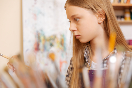 Involved young girl practicing painting in the art school Stock Photo