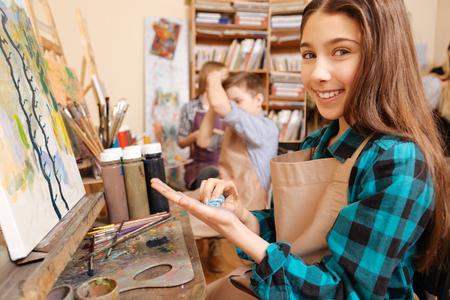 Chica encantada disfrutando de la pintura en el estudio de arte Foto de archivo - 74445512