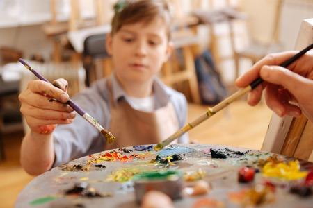 Skilled artist teaching painting kid in the studio