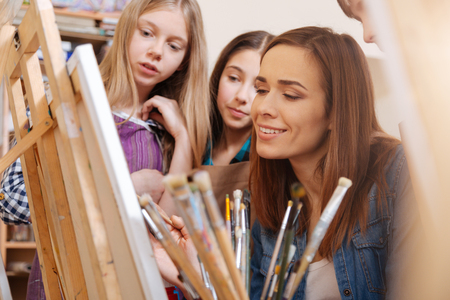Creative woman teaching young capable generation in the art studio