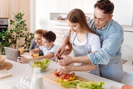 Beau père aimant qui donne ses leçons de cuisine à la fille Banque d'images